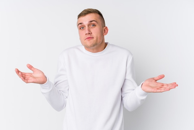 Junger kaukasischer mann auf weißer wand schultern in fragender geste zweifelnd und zuckend.