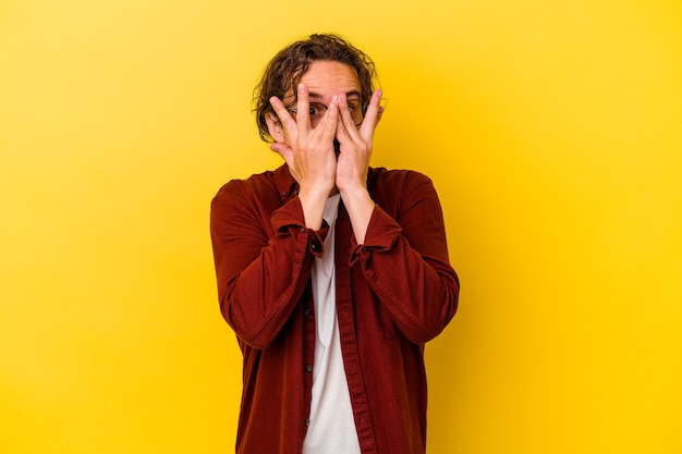 Junger kaukasischer mann blinzelt in die kamera durch finger, verlegenes bedeckendes gesicht.