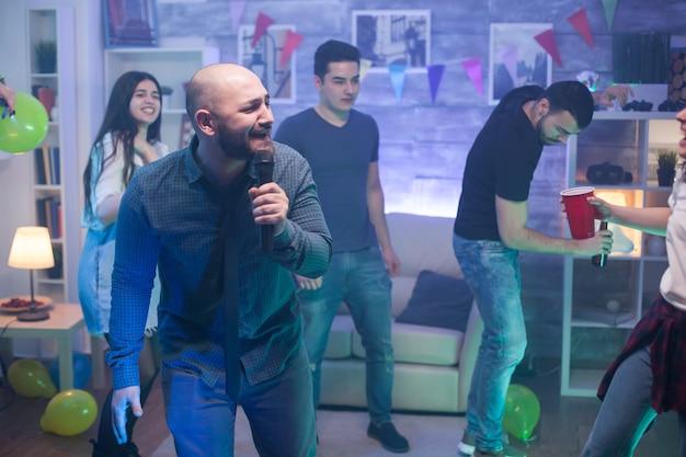 Junger kaukasischer mann, der am mikrofon für die unterhaltung seiner freunde auf der party singt.