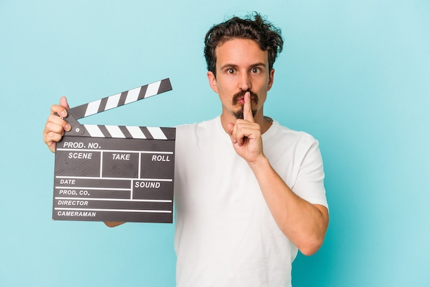 Junger kaukasischer mann, der auf blauem hintergrund eine klappe hält, die ein geheimnis hält oder um stille bittet.