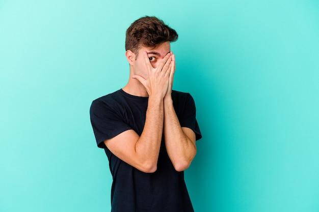 Junger kaukasischer mann, der auf blauer wand isoliert blinzelt durch finger erschrocken und nervös.