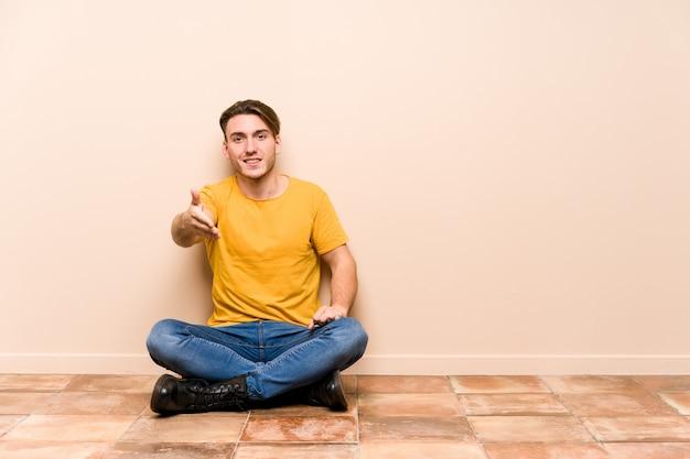 Junger kaukasischer mann, der auf dem boden lokalisierte streckende hand in der grußgeste sitzt.