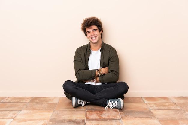 Junger kaukasischer mann, der auf dem boden mit den armen gekreuzt sitzt und vorwärts schaut