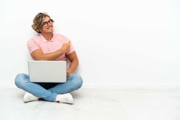 Junger kaukasischer mann, der auf dem boden mit seinem laptop lokalisiert sitzt