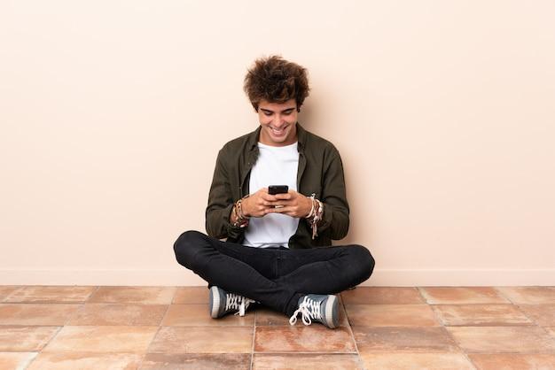 Junger kaukasischer mann, der auf dem boden sendet eine mitteilung mit dem mobile sitzt