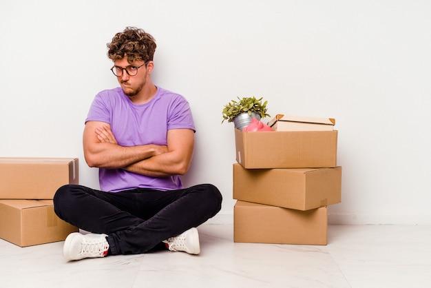 Junger kaukasischer mann, der auf dem boden sitzt, bereit, sich isoliert auf weißem wandrunzeln stirnrunzelndes gesicht in missfallen zu bewegen, hält arme verschränkt.