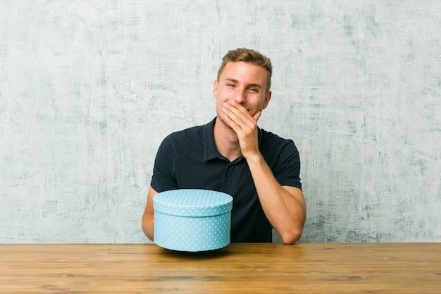 Junger kaukasischer mann, der auf einem tisch eine geschenkbox lacht über etwas, mund mit den händen bedeckend hält.