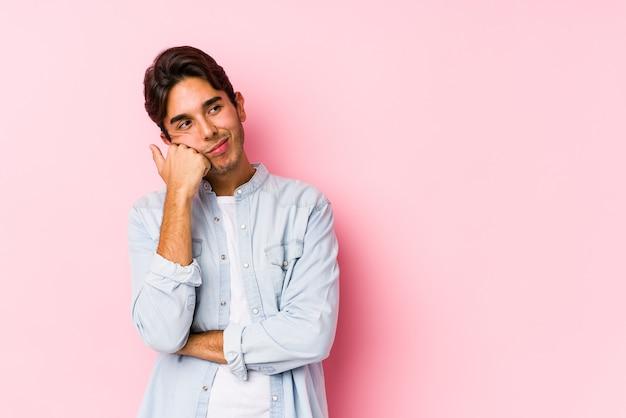 Junger kaukasischer mann, der auf rosa isoliert aufwirft, der sich traurig und nachdenklich fühlt und kopienraum betrachtet.