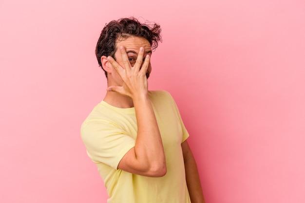 Junger kaukasischer mann, der auf rosafarbenem hintergrund isoliert ist, blinzelt durch die finger in die kamera, verlegen das gesicht.