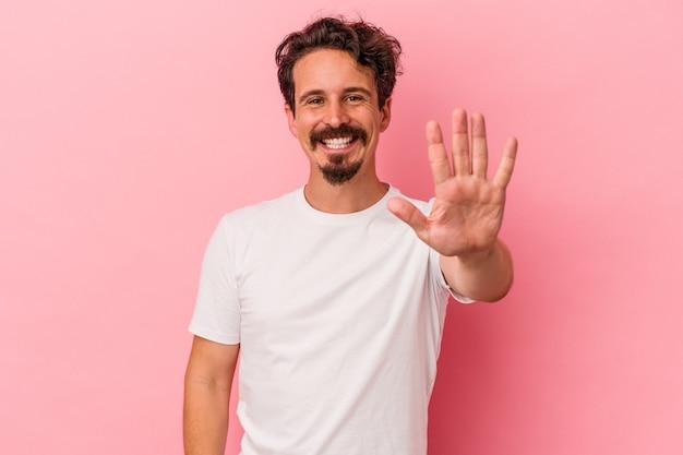 Junger kaukasischer mann, der auf rosafarbenem hintergrund isoliert ist, lächelt fröhlich und zeigt nummer fünf mit den fingern.