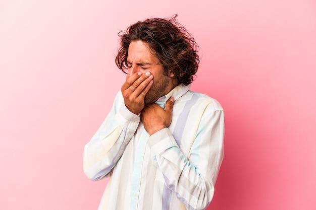 Junger kaukasischer mann, der auf rosafarbenem hintergrund isoliert ist, leidet an halsschmerzen aufgrund eines virus oder einer infektion.
