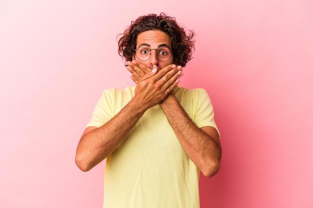 Junger kaukasischer mann, der auf rosafarbenem hintergrund isoliert ist, schockiert, den mund mit den händen zu bedecken