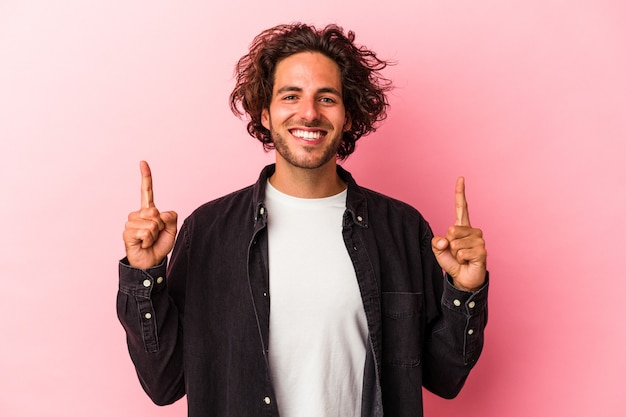Junger kaukasischer mann, der auf rosafarbenem hintergrund isoliert ist, zeigt an, dass beide vorderfinger eine leerstelle zeigen.