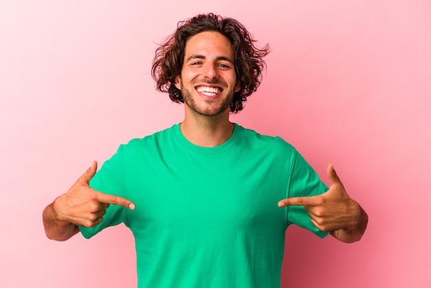 Junger kaukasischer mann, der auf rosafarbenem hintergrund isoliert ist, zeigt mit den fingern nach unten, positives gefühl.