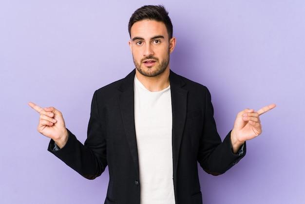 Junger kaukasischer mann, der auf verschiedene kopienräume zeigt, einen von ihnen wählend zeigt, mit dem finger zeigend.
