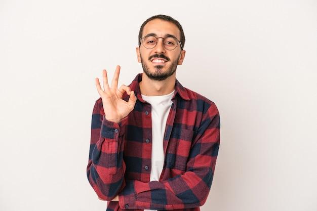 Junger kaukasischer mann, der auf weißem hintergrund lokalisiert wird, zwinkert ein auge und hält eine okaygeste mit der hand.