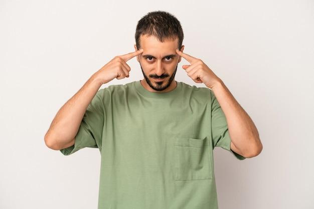 Junger kaukasischer mann, der auf weißem hintergrund lokalisiert wurde, konzentrierte sich auf eine aufgabe und hielt die zeigefinger, die den kopf zeigen.