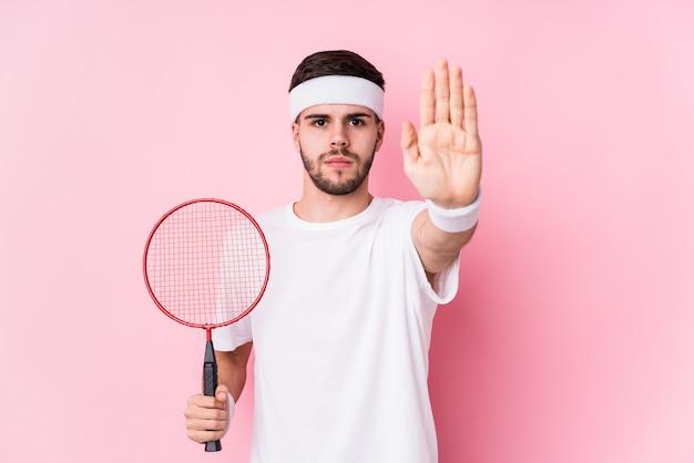 Junger kaukasischer mann, der badminton spielt, isoliert stehend mit ausgestreckter hand, die stoppschild zeigt und sie verhindert.