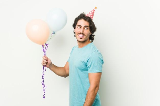 Junger kaukasischer mann, der ballons hält, die einen brithday feiern, der in einer grauen wand lokalisiert wird