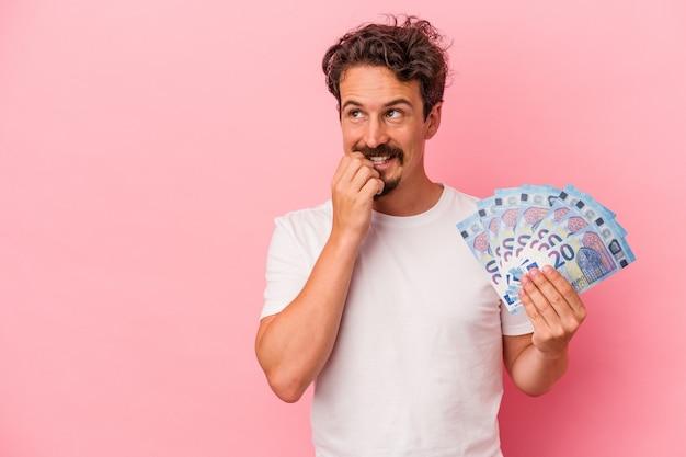 Junger kaukasischer mann, der banknoten einzeln auf rosafarbenem hintergrund hält, entspannte sich beim nachdenken über etwas, das einen kopienraum betrachtet.
