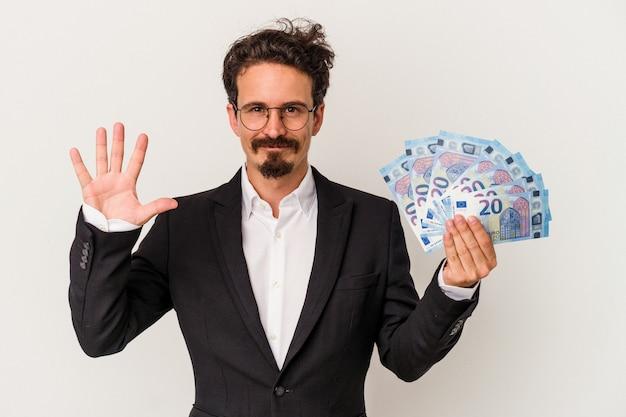 Junger kaukasischer mann, der banknoten hält, die auf weißem hintergrund lokalisiert werden, lächelt fröhlich und zeigt nummer fünf mit den fingern.