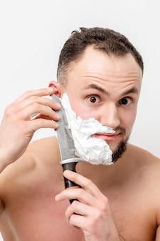 Junger kaukasischer mann, der bart mit messer auf weißem hintergrund rasiert