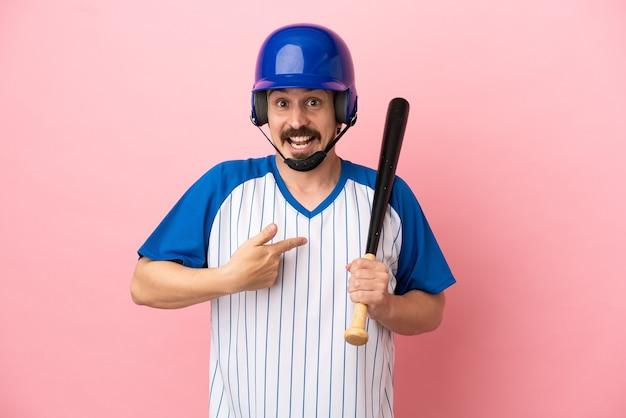 Junger kaukasischer mann, der baseball auf rosafarbenem hintergrund mit überraschtem gesichtsausdruck spielt