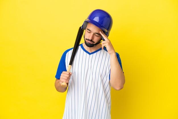 Junger kaukasischer mann, der baseball isoliert auf gelbem hintergrund mit kopfschmerzen spielt