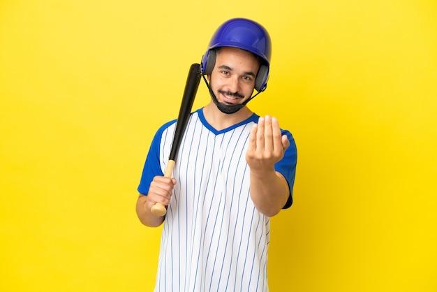 Junger kaukasischer mann, der baseball spielt, isoliert auf gelbem hintergrund, der einlädt, mit der hand zu kommen. schön, dass du gekommen bist