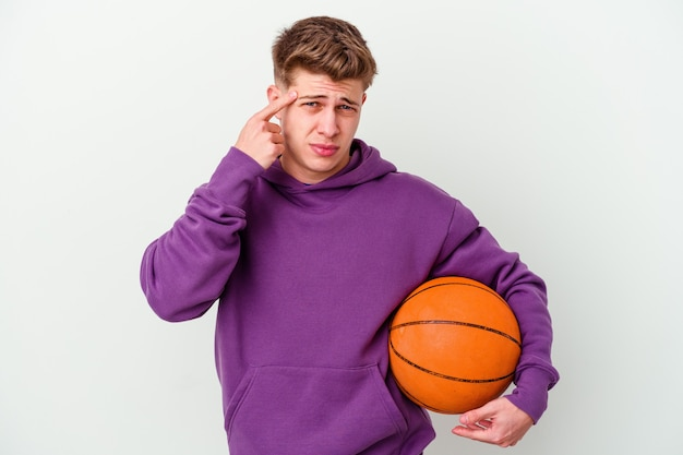 Junger kaukasischer mann, der basketball isolierte wand spielt, die eine enttäuschungsgeste mit zeigefinger zeigt.