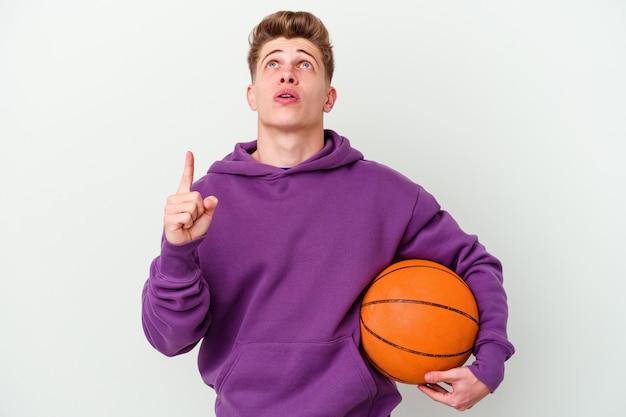 Junger kaukasischer mann, der basketball isolierte wand spielt, die oben mit geöffnetem mund zeigt