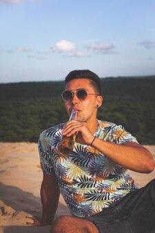 Junger kaukasischer mann, der bier an der spitze einer sanddüne trinkt.