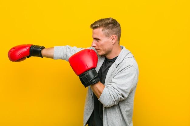 Junger kaukasischer mann, der boxhandschuhe trägt