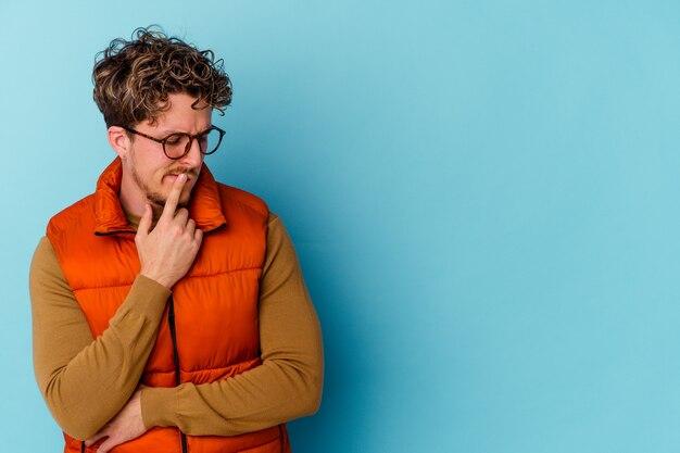 Junger kaukasischer mann, der brillen trägt, die auf blaue wand lokalisiert werden, die seitwärts mit zweifelhaftem und skeptischem ausdruck schaut.