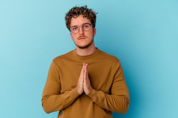 Junger kaukasischer mann, der brillen trägt, die auf der blauen wand isoliert beten, die hingabe zeigt, religiöse person, die nach göttlicher inspiration sucht.