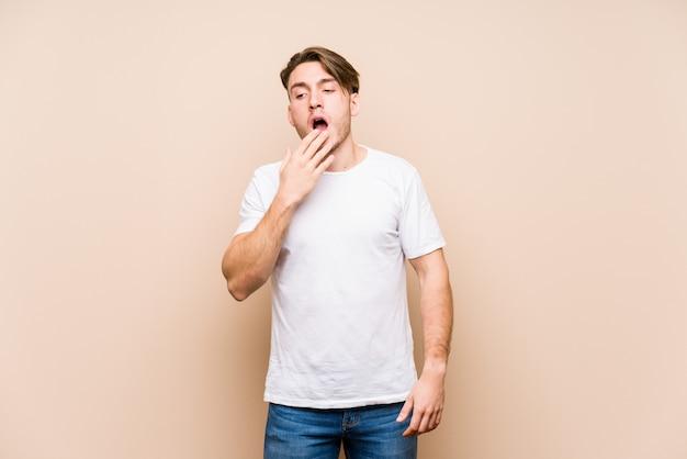 Junger kaukasischer mann, der das lokalisierte gähnen zeigt einen müden gestenbedeckungsmund mit der hand aufwirft.