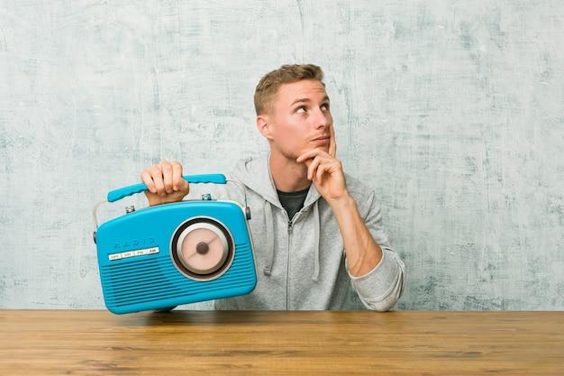 Junger kaukasischer mann, der das radio hört, das mit zweifelhaftem und skeptischem ausdruck seitwärts schaut.