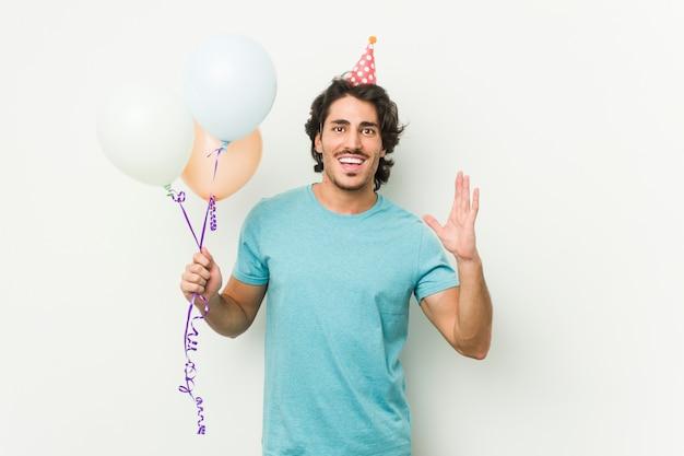Junger kaukasischer mann, der die ballone feiern einen brithday lokalisiert in einer grauen wand hält
