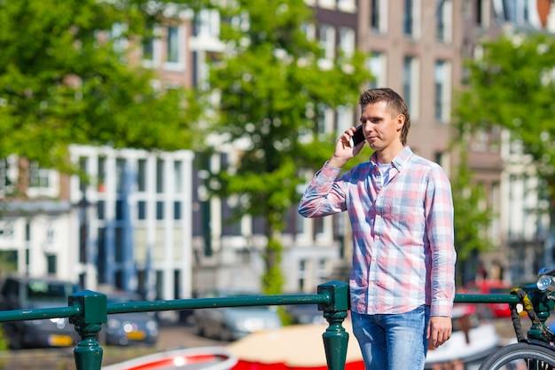 Junger kaukasischer mann, der durch handy auf brücke in der europäischen stadt spricht