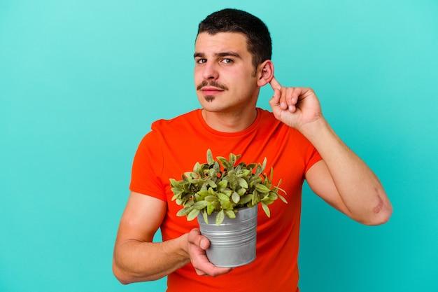 Junger kaukasischer mann, der ein blatt lokalisiert auf blauer wand hält, die versucht, einen klatsch zu hören