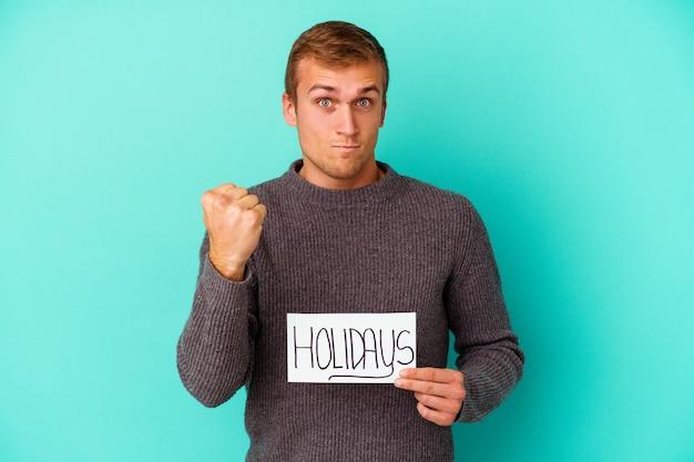 Junger kaukasischer mann, der ein feiertagsplakat hält, das auf blauem hintergrund isoliert ist und die faust zur kamera zeigt, aggressiver gesichtsausdruck.