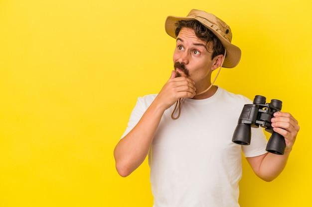 Junger kaukasischer mann, der ein fernglas isoliert auf gelbem hintergrund hält und seitlich mit zweifelhaftem und skeptischem ausdruck schaut.