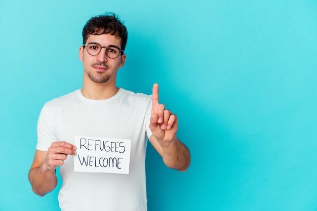 Junger kaukasischer mann, der ein flüchtlings-willkommensplakat isoliert hält, das nummer eins mit finger zeigt