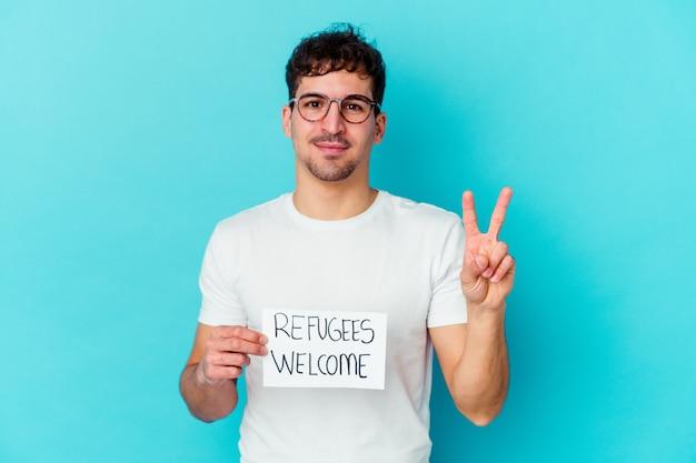 Junger kaukasischer mann, der ein flüchtlings-willkommensplakat isoliert hält, das nummer zwei mit den fingern zeigt.