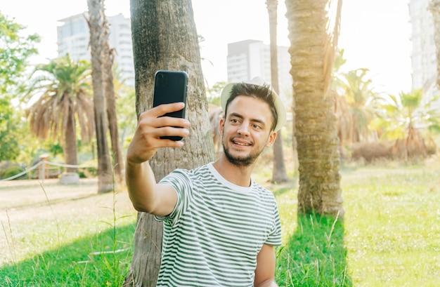 Junger kaukasischer mann, der ein foto in einem park mit einer stadt im hintergrund macht