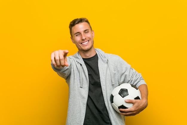 Junger kaukasischer mann, der ein freundliches lächeln des fußballs zeigt auf front hält.