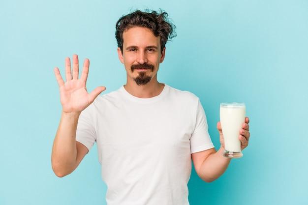 Junger kaukasischer mann, der ein glas milch auf blauem hintergrund isoliert hält, lächelt fröhlich und zeigt nummer fünf mit den fingern.