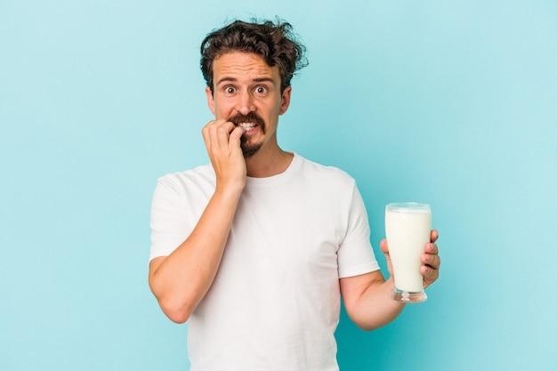 Junger kaukasischer mann, der ein glas milch einzeln auf blauem hintergrund hält, beißt fingernägel, nervös und sehr ängstlich.