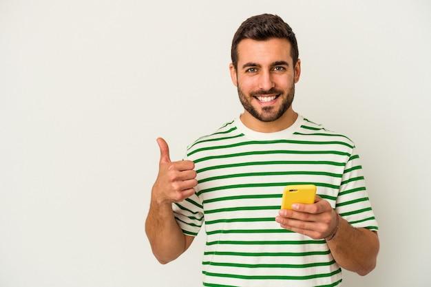 Junger kaukasischer mann, der ein handy lokalisiert, das auf weißem hintergrund lokalisiert lächelt und daumen oben anhebt