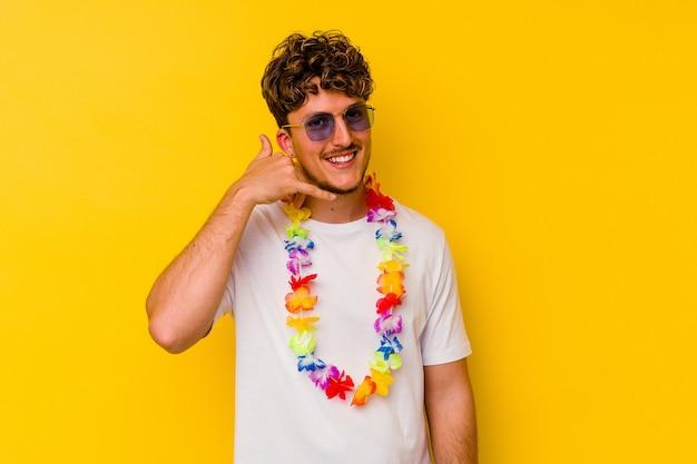 Junger kaukasischer mann, der ein hawaiianisches partyzeug trägt, das auf gelbem hintergrund isoliert ist und eine handy-anrufgeste mit den fingern zeigt.